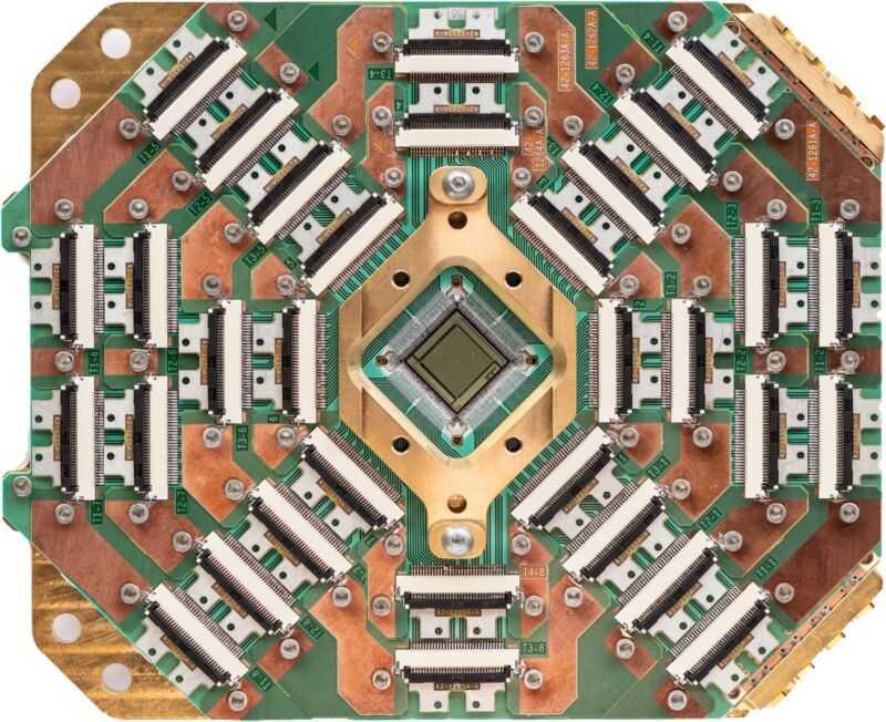 Изображение микросхемы, окруженной сложным вспомогательным оборудованием.