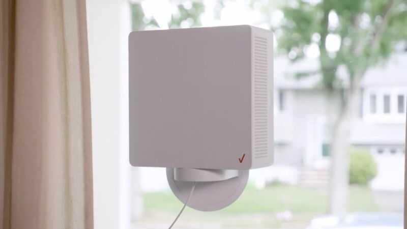 Домашнее интернет-устройство Verizon 5G, установленное внутри окна в доме на жилой улице.