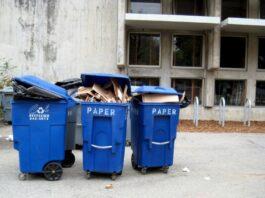 Ряд синих баков для переработки бумаги, набитых картоном.