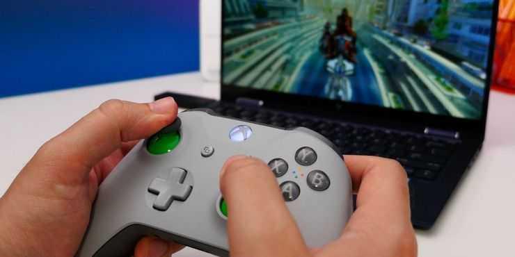 Xbox one: человек, который играет в видеоигры с помощью контроллера Xbox на своем ПК